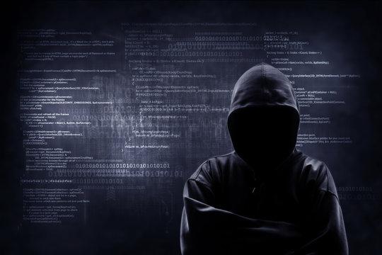 Internet crime concept. Hacker working on a code on dark digital background with digital interface around.