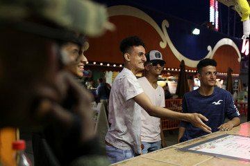 Yemeni American, Shaya Ahmed (center), 17, tries his luck at a game on Eid Al-Fitr at Luna Park in Coney Island, Brooklyn, New York