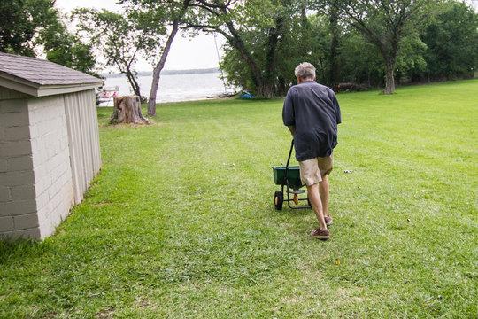 Man applying fertilizer to the lawn