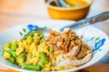 Green Curry spicy Chicken cuisine with long bean, coconut milk in Thai call Kaeng Kiew Wan Kai and fried pork with garlic pepper on rice favorite delicious Thai food