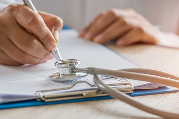 Healthcare medical concept, Hands Doctor's writing and working on prescription clipboard with record information paper folders on desk in hospital or clinic. Focus stethoscope on file papers