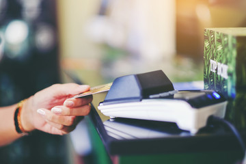 Close up of woman hand holding credit card at the supermarket checkout, she is paying using a credit card, shopping and retail concept