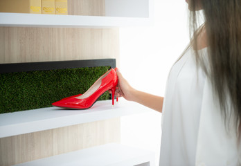 Women is picking the red high-heeled shoes from the shelves