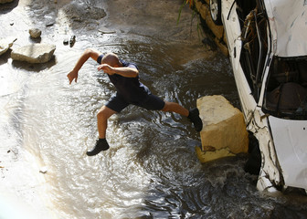A Civil Protection rescuer jumps off a heavily damaged car which had been carried away by flash floods in Birkirkara