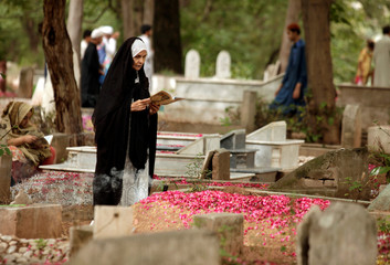 A woman prays next to the grave of a relative on the first day of Eid al-Fitr, at a cemetery in Rawalpindi