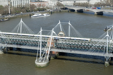 Aerial view of Hungerford Bridge, a steel truss railway bridge, flanked by the Golden Jubilee Bridges, two cable-stayed pedestrian bridges over the River Thames in London, England, UK