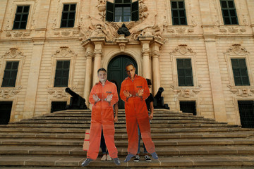 Activists from anti-corruption group Il-Kenniesa carry cardboard cut-outs of Mizzi and Schembri during a protest marking eight months since the assassination of anti-corruption journalist Daphne Caruana Galizia, in Valletta