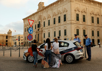 Activists from anti-corruption group Il-Kenniesa are questioned by police after a protest marking eight months since the assassination of anti-corruption journalist Daphne Caruana Galizia, in Valletta