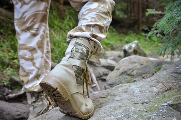 Close up of a military man in trekking shoes going on a rocky path in the forest.