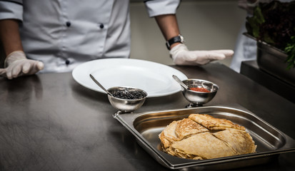 Pancakes and two kinds of caviar in metal dishes on a professional restaurant kitchen. Hands of Chef. Selective focus. Shallow depth of field. Toned