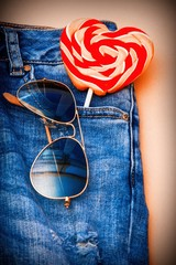 heart lollipop and sunglasses in the blue jean pocket