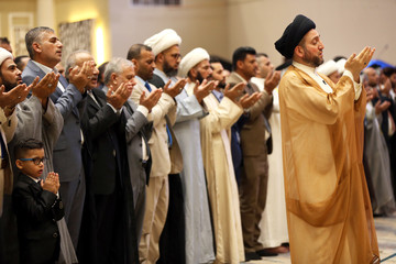 Ammar al-Hakim, leader of the Hikma Current, leads prayers for the Muslim festival of Eid al-Fitr at his headquarters in Baghdad