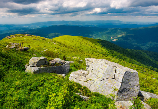 boulders on grassy hills. beautiful mountainous landscape. distant mountain under the cloudy sky. view in to the valley from the top of Runa mountain