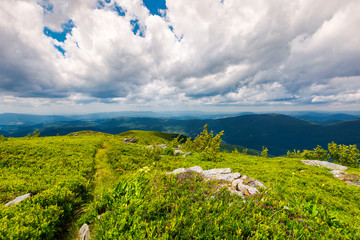 path along the grassy slope on top of a mountain. lovely summer landscape. wonderful place for hiking and camping. cloudy sky above the mountain ridge in the distance