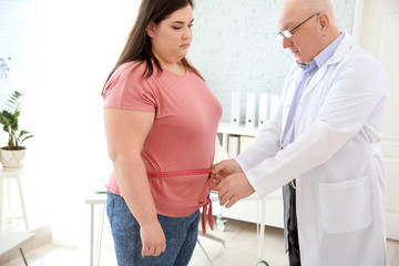 Male doctor measuring waist of overweight woman in clinic