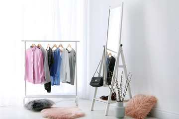 Rack with clothes and modern mirror in light room