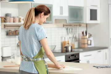 Woman rolling dough at table in kitchen