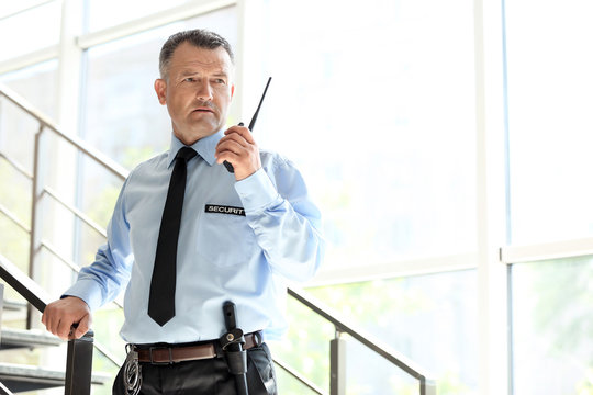 Male security guard using portable radio transmitter indoors