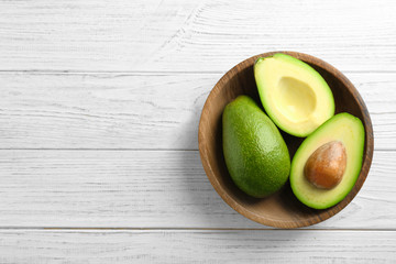 Bowl with ripe avocados on wooden background, top view