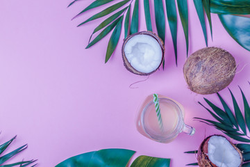 Coconut water and coconuts on a bright pastel background.
