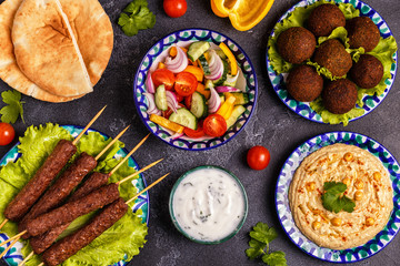 Classic kebabs, falafel and hummus on the plates.
