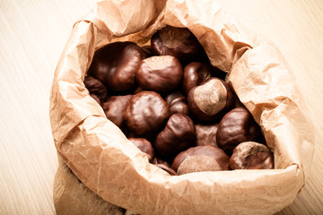 Chestnuts in a paper bag on a light wooden table. Toned
