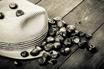 Chestnuts and mens hat on a old wooden table. Toned