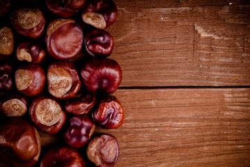 Lot of chestnuts on the old wooden background. Toned