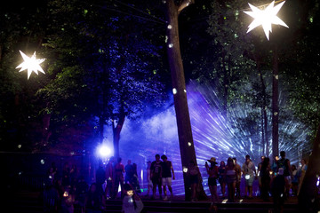 Revelers walk through the concert grounds on the second day of the Firefly Music Festival in Dover, Delaware