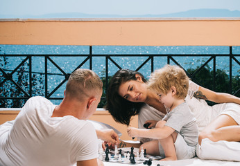 Little boy and his father with mother playing chess