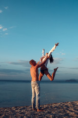 Couple in love dancing, having fun, sea and skyline background. Couple in love stand on beach, seashore. Honeymoon, just married concept. Man carries woman, couple happy on vacation