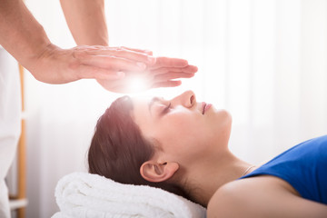 Therapist Performing Reiki Healing Treatment On Woman