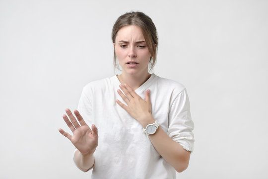 European woman in white t-shirt having a sore throat. Lost a voice. Problem with health.