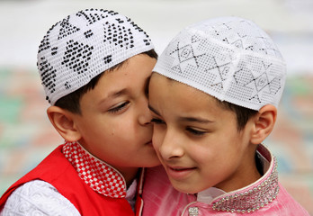 Children greet each other after offering Eid al-Fitr prayers marking the end of the holy fasting month of Ramadan at a mosque, in Jammu