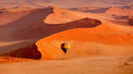 Hot air balloon in flight against orange sand dunes in Sossusvlei Namibia
