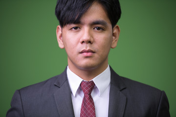 Young handsome Asian businessman against green background