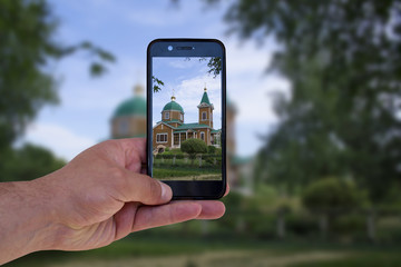 man takes pictures of church on mobile phone