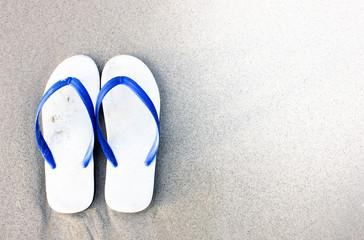 Slipper on the beach, sandals on the beach. Flipflops on a sandy ocean beach - summer vacation concept. Beach summer casual shoes. Copy space