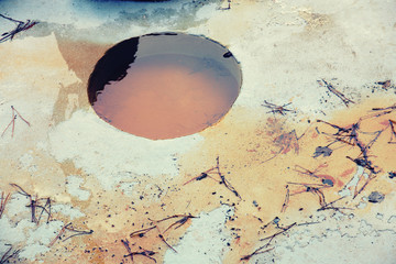 rounded hole covered by dirty water