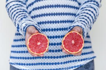 Juicy grapefruit cut on half in hands, healthy eating concept