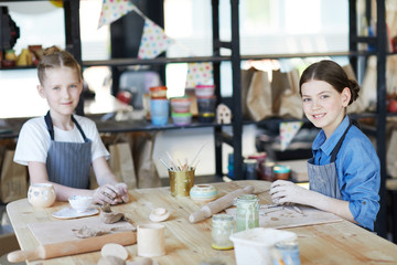 Two youthful schoolgirls looking at you while siting by table and kneading clay to make handcraft