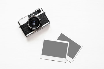 Flatlay vintage retro camera on wooden white background with empty instant paper photo placed your pictures. Top view