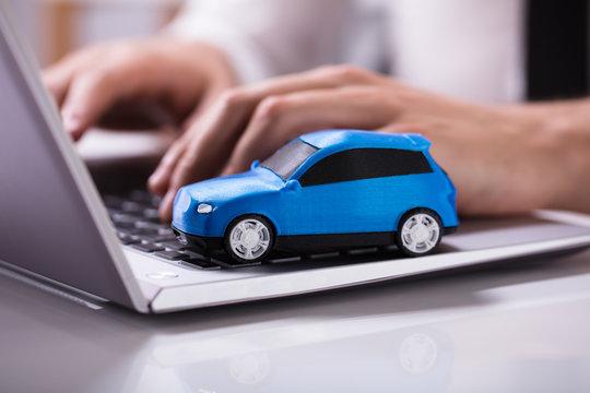 Blue Car On Laptop Keypad