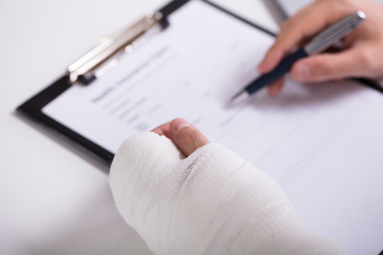 Person With Fractured Hand Filling Health Insurance Form