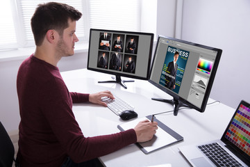 Designer Drawing On Graphic Tablet While Working On Computer