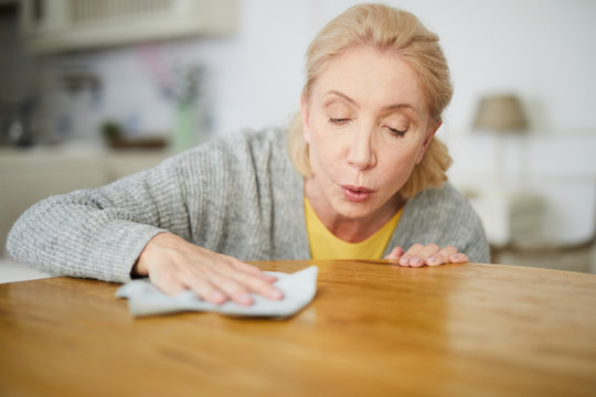 Senior housewife blowing dust from wooden table while rubbing it with duster