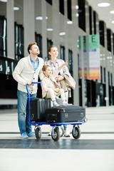 Little girl pointing at timetable with departure data while sitting on baggage cart with her mother and father near by