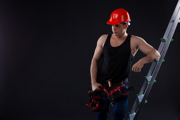 Worker leans on a ladder and looks up on a black background