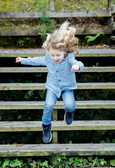 Happy blond child jumping wooden stairs
