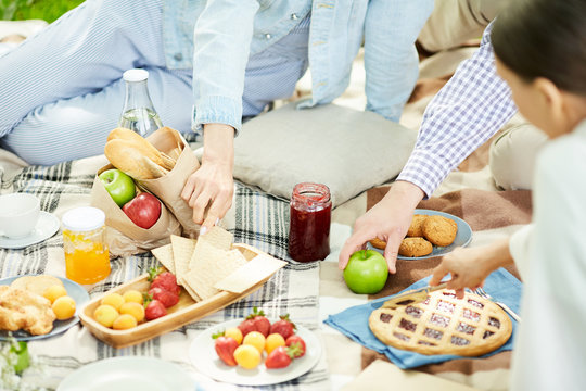 Fresh strawberries, fruits, pie, cookies and jam on picnic cloth and family having lunch